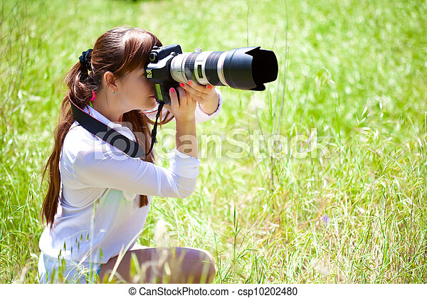 A woman with a camera in the field - csp10202480