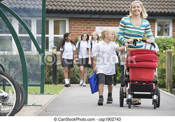 A woman with a pushchair walking her son home from school - csp1902743