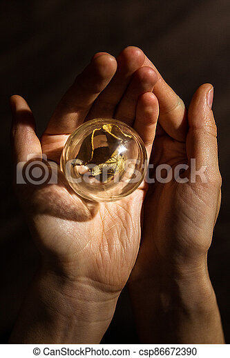 A wonderful wonderful world in the palm of your hand. A piece of nature under glass. The concept of a child's play with glass. - csp86672390