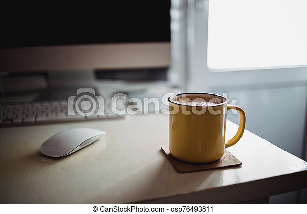 A yellow cup of coffee stands on the office desk in the sunny morning-evening light, next to the monitor and keyboard - csp76493811
