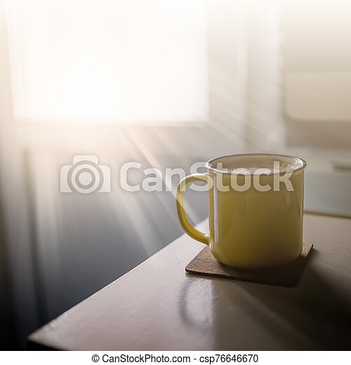 A yellow cup of coffee stands on the office desk in the sunny morning-evening light, next to the monitor and keyboard - csp76646670