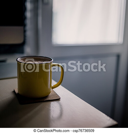 A yellow cup of coffee stands on the office desk in the sunny morning-evening light, next to the monitor and keyboard - csp76736509