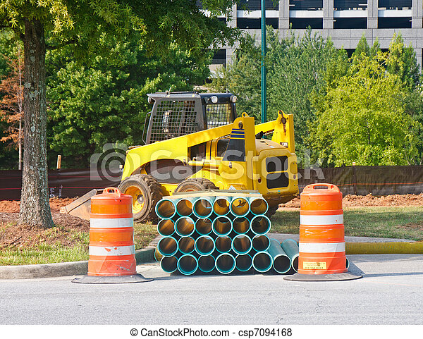 A yellow front end loader behind pipes and orange barrels - csp7094168