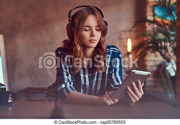 A young charming sensual woman listening to a music in headphones. A young charming sexy woman in a room with a loft interior   CanStock