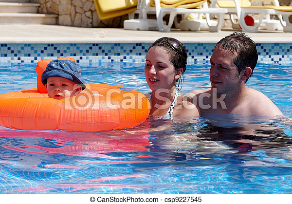 A young couple and baby in a pool - csp9227545