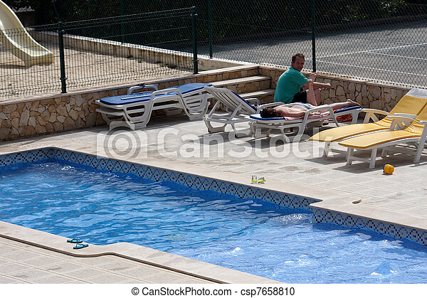 A young couple by the pool - csp7658810