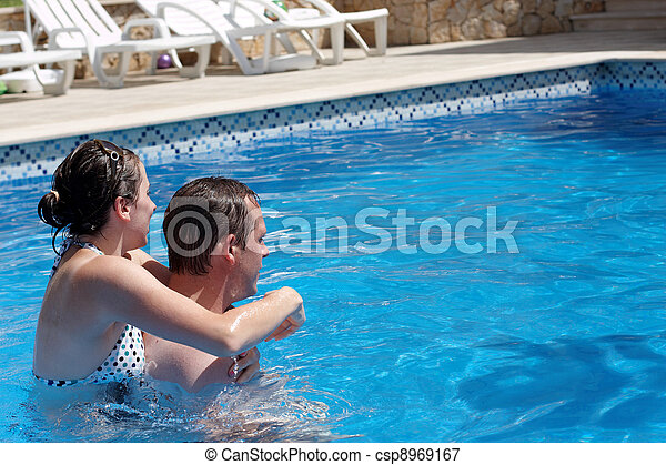 A young couple in the swimming  pool - csp8969167