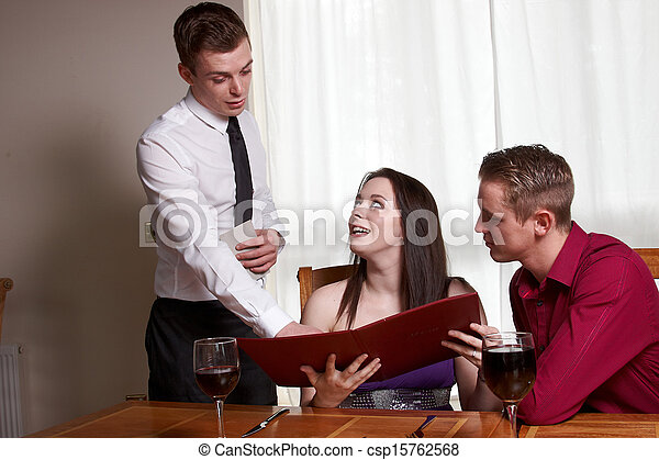 A young couple reading a menu - csp15762568