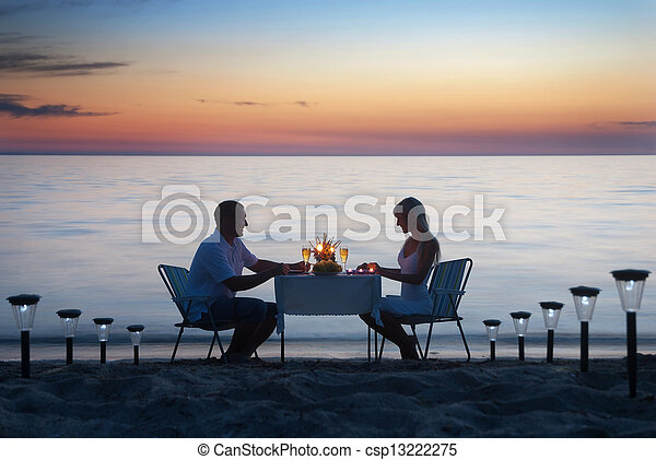 A young couple share a romantic dinner with candles and wine glasses on the sea sand beach - csp13222275