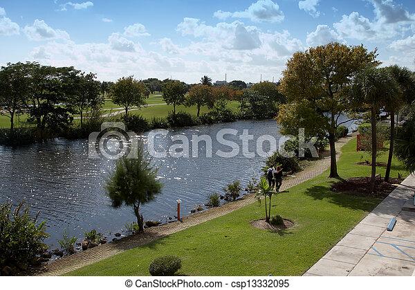 A young couple walking along a river - csp13332095