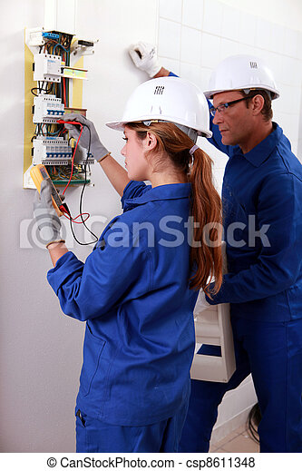 a young female electrician using an ammeter for checking an electricity meter and an older man watching her - csp8611348