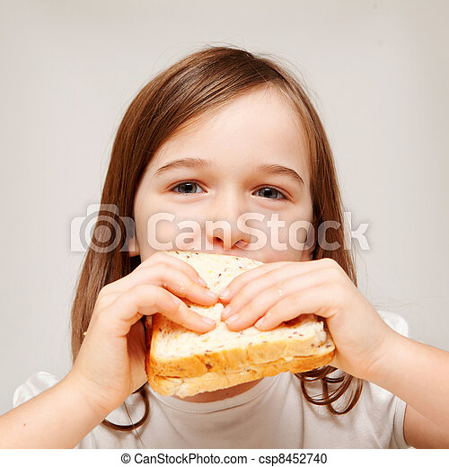 A young girl enjoys a sandwhich consisting of wholemeal bread. - csp8452740
