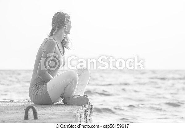 A young girl sits on a pier and looks out into the distance at sea - csp56159617
