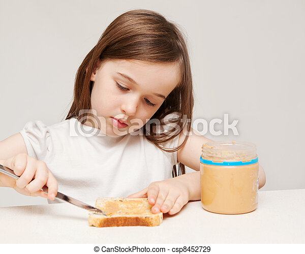 A young girl spreads peanut butter onto a piece of wholemeal bread. - csp8452729