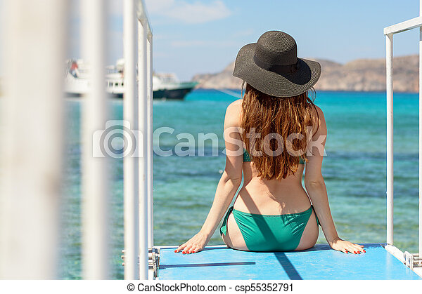 A young girl with a hourglass figure sits on a pier and looks into the sea. wearing a green swimsuit and a black hat. rear view. - csp55352791