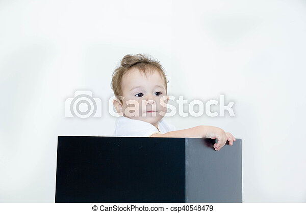 A young infant boy peeking out of a box on a white background - csp40548479