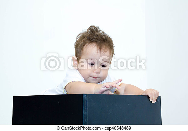 A young infant boy peeking out of a box on a white background - csp40548489