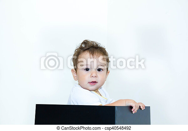 A young infant boy peeking out of a box on a white background - csp40548492