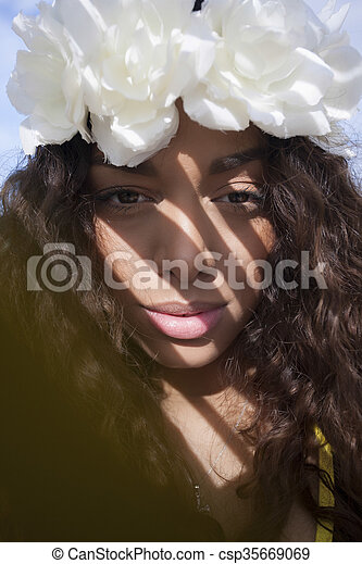 f851423d31 A young lady wearing a flower crown. Crowned girl smiling on the beach.