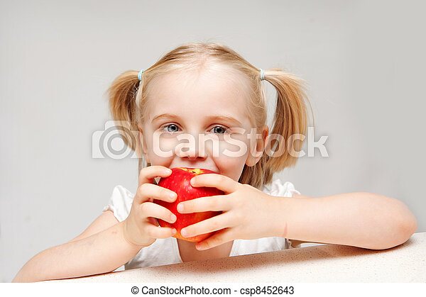 A young little blonde girl takes a bite of a big red apple. - csp8452643