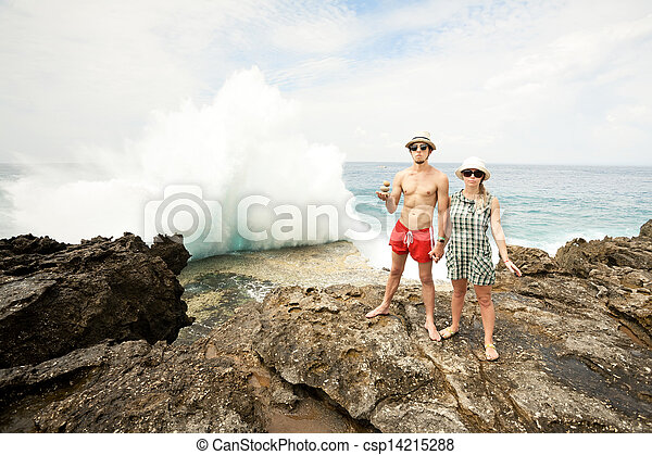 A young man and woman in the seacoast, huge wave crashing on the rocks in the background. Three round stones in a hands of man. - csp14215288