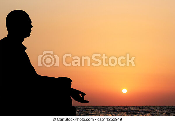 A young man sitting in lotus position and meditating on a beach in the evening with sun setting in the background. The sky is orange yellow and the ocean can also be seen in the meditation backdrop - csp11252949