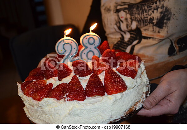 A young married man cuts his birthday cake with strawberries