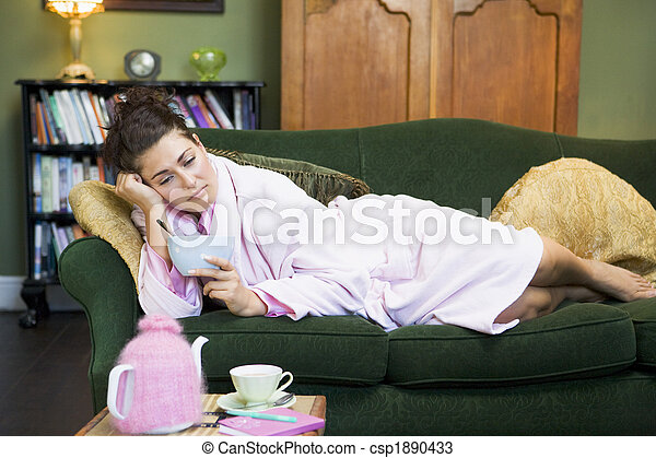 A young woman lying on her couch eating cereal - csp1890433