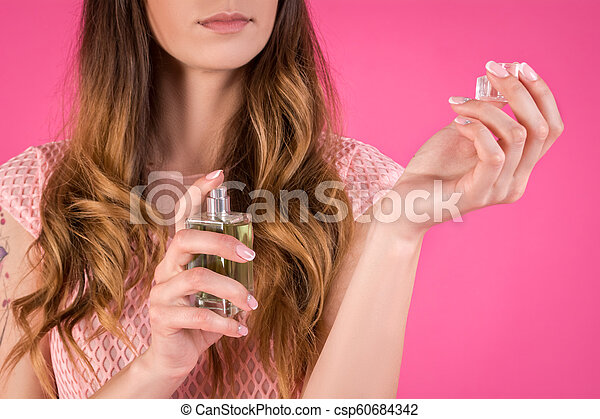 A young woman uses perfume. Girl on a pink background - csp60684342