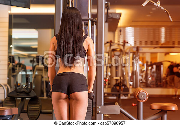 A young woman working out on a machine in the Gym - csp57090957