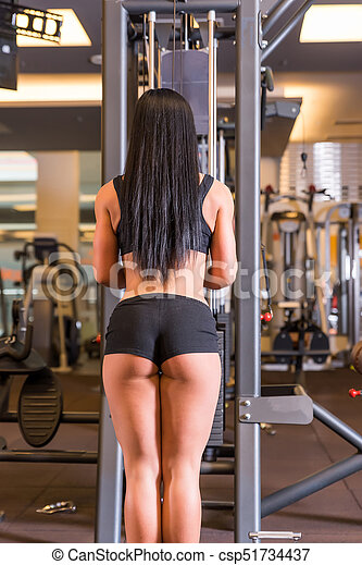 A young woman working out on a machine in the Gym - csp51734437