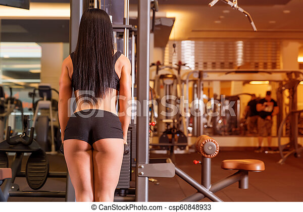 A young woman working out on a machine in the Gym - csp60848933