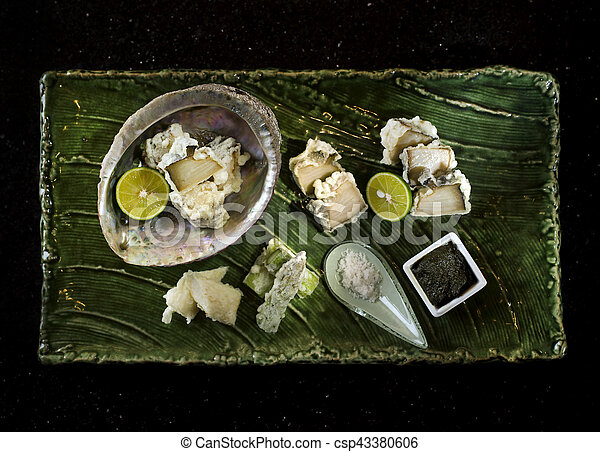 Abalone tempura with black sauce, lemon and salt on wooden tray in black background - csp43380606