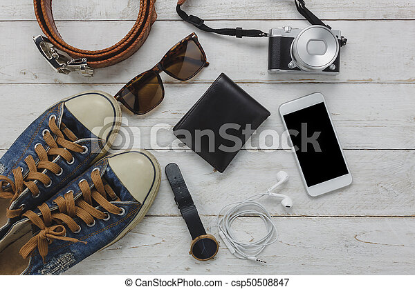 Above view of necessary items travel and technology background concept. Important accessory for travel and teenage or adult. Mix several objects on modern rustic white wooden home office desk. - csp50508847