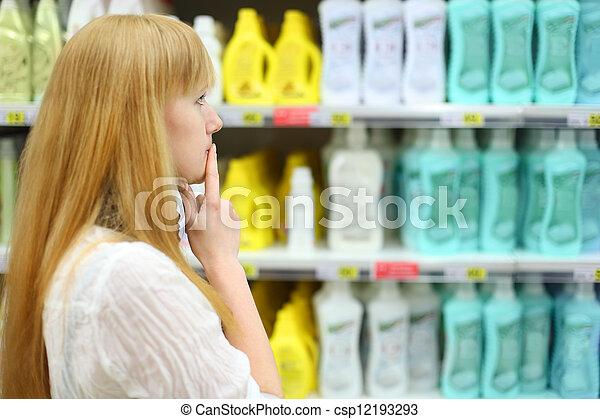 La chica rubia elige el abstáculo en la tienda, profundidad superficial del campo - csp12193293