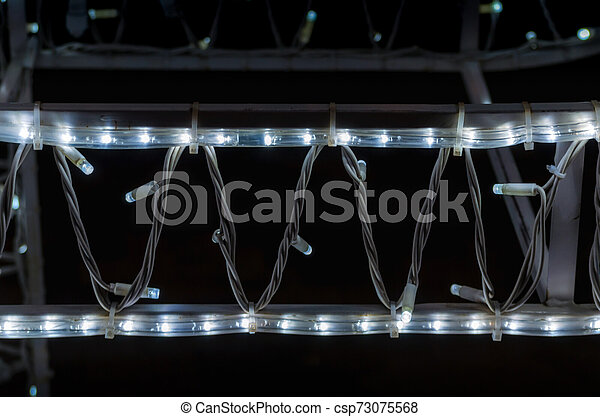 abstract background pattern small lamps on a black background close up - csp73075568