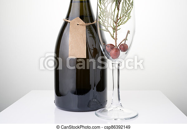 Abstract Christmas background with a bottle of champagne and a Glass with a coniferous branch on a light background. - csp86392149