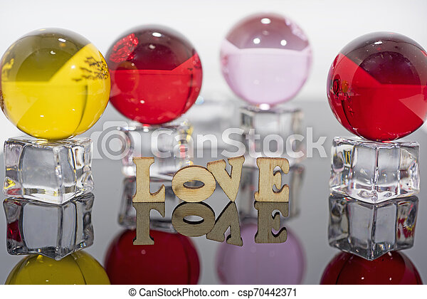 Abstract composition of love. Isolated wooden letters and glass balls. - csp70442371