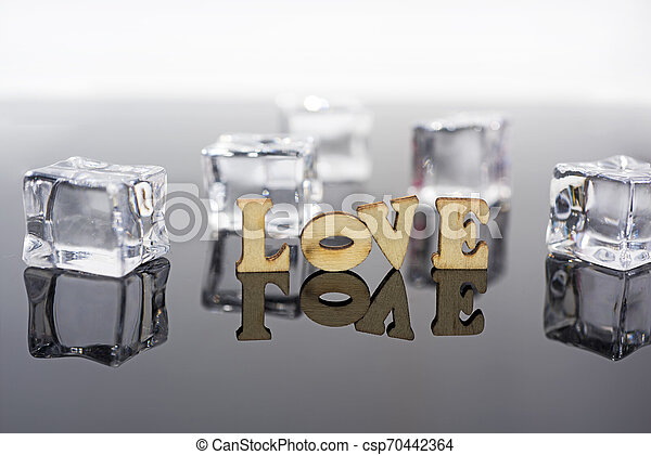 Abstract composition of love. Isolated wooden letters and glass balls. - csp70442364