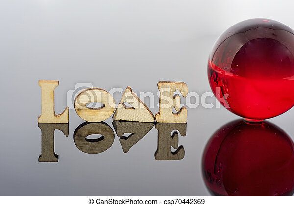 Abstract composition of love. Isolated wooden letters and glass balls. - csp70442369
