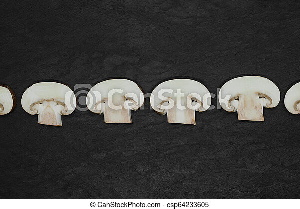 Abstract composition of split up brown champignons mushrooms placed in line on stone background surface - csp64233605