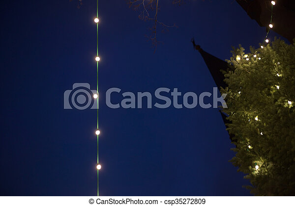 abstract night shot of light string christmas tree and church
