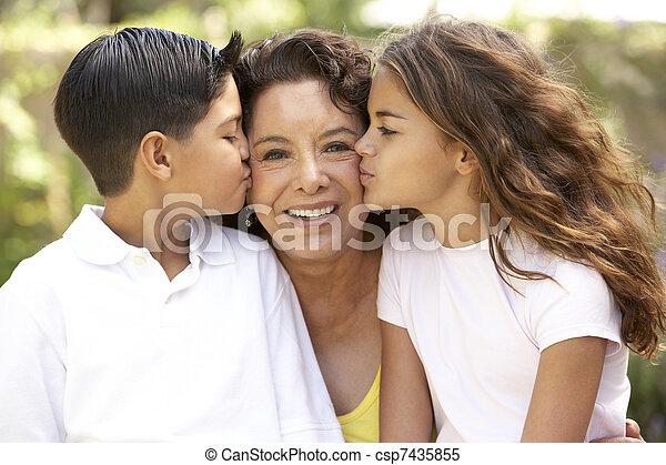 Abuela con nietos en el jardín - csp7435855