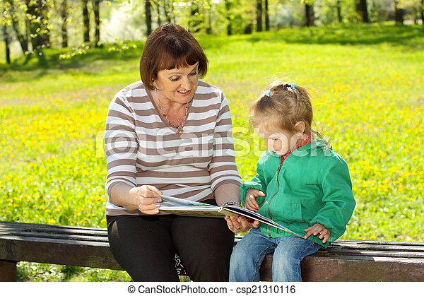 Abuela y nieta leyendo un libro al aire libre - csp21310116