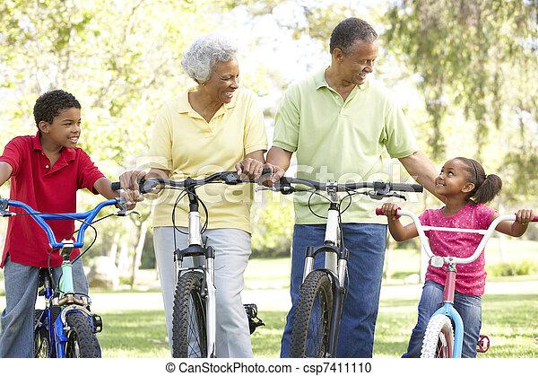 Abuelos en el parque con nietos en bicicleta - csp7411110