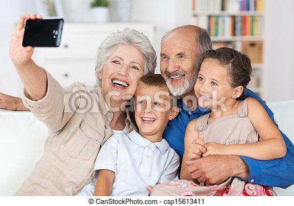 Abuelos y nietos con una cámara - csp15613411