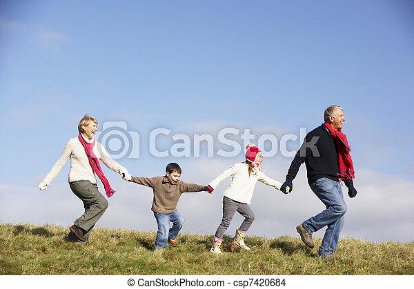Abuelos y nietos corriendo en el parque - csp7420684