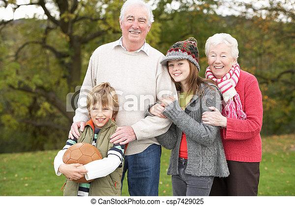 Abuelos con nietos sosteniendo el fútbol afuera - csp7429025