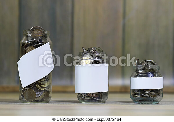 Accumulated coins stacked in glass jars - csp50872464