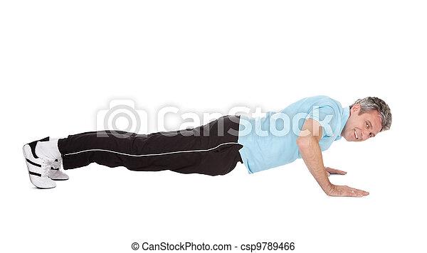 Active mature man doing pushups - csp9789466